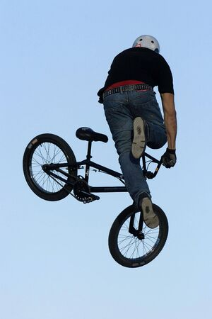 performs: A male BMX cyclist performs a trick off a big jump. Stock Photo