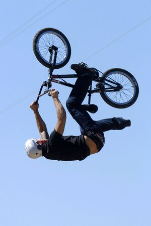 performs: A male youth BMX rider performs a backflip.
