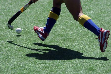 hockey cesped: Un jugador del hockey del campo funciona con la bola y el palillo.