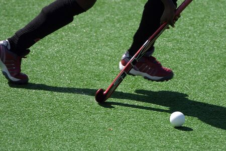 the runs: A field hockey player runs with the ball and stick.