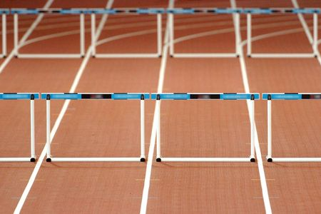 hurdles: An empty track with hurdles waiting for a race to begin.