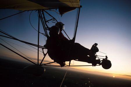 airplane ultralight: Two pilots fly in an ultralight plane.