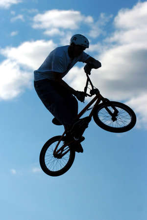 A BMX extreme rider preforms a trick against a blue sky with clouds. Stock Photo - 708364