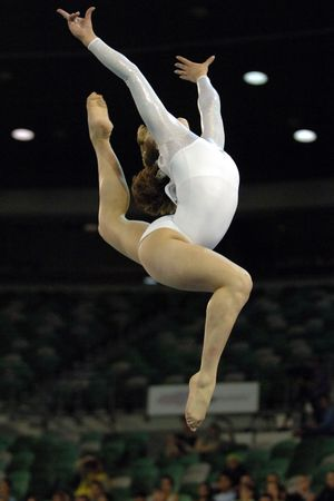 A female gymnast leaps into the air during a floor routine during competition. Stock Photo - 708367