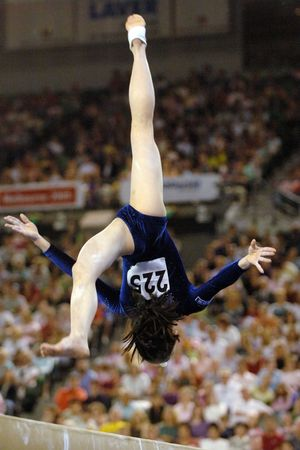 female gymnast: A female gymnast preforms a routine on the balance beam during competition.