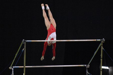 A female gymnast preforms a routine on the uneven bars during competition.