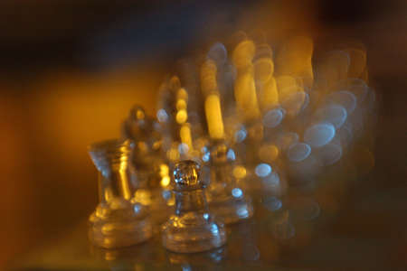 blurr: Glass chess pieces sit in the dark on a chess board.