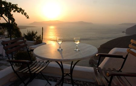 santorini greece: The sun sets over the caldera in Santorini, Greece with two wine glasses places nicely on the table.