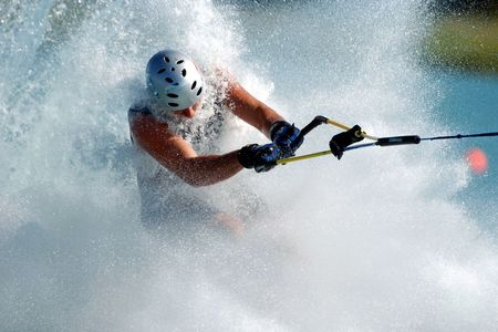 splashed: Barefoot waterskier is splashed by all the water spray coming up off the wake.