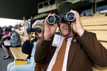 spectators: Los espectadores de ver una carrera de caballos con binoculares desde las gradas.