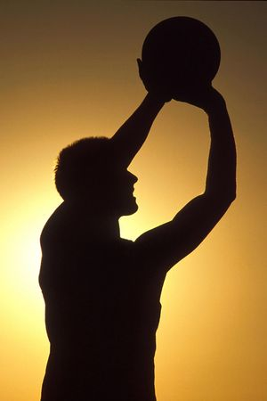 A silhouette basketball player shoots for a basket. photo