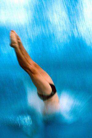 Un plongeur est de plonger dans la piscine durant la compétition.