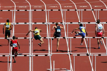 hurdles: Six lanes of men run over the hurdles in a race.