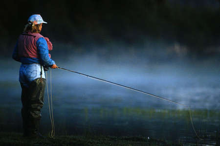 steamy: A man fly fishes alone on a steamy river.