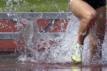 steeplechase: A steeplechase runner splashes through the water.