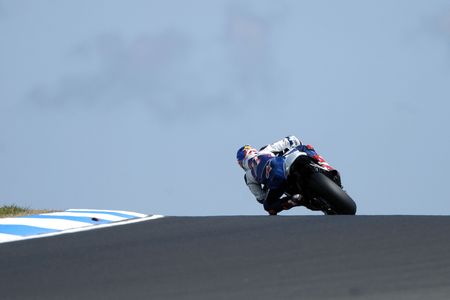 goes: A MotoGP rider goes over the crest of a hill at high speed.