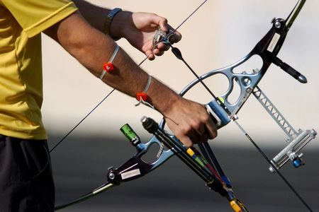 bow and arrow: Hands hold an archery bow and arrow ready to aim at a target.