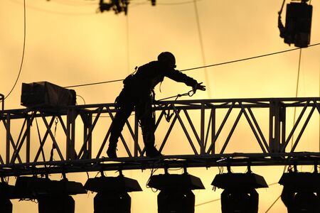 rigging: A silhouetted construction worker fixes lines on rigging at sunset.