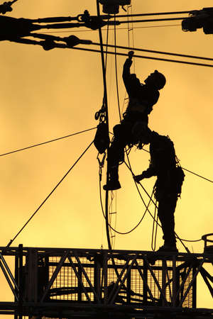 A silhouetted construction workers fix lines on rigging at sunset.