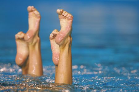swimming costumes: Feet and legs of a synchronized swimming pair sticking out of the pool during competition. Stock Photo