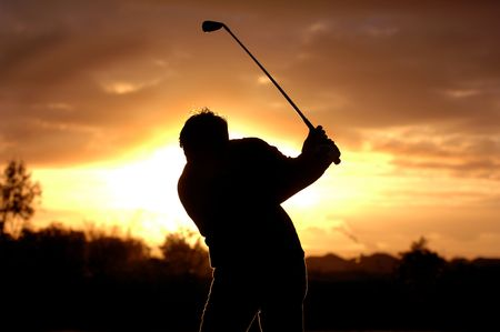 A left handed golfer practices early morning with a beautiful sunrise.  photo