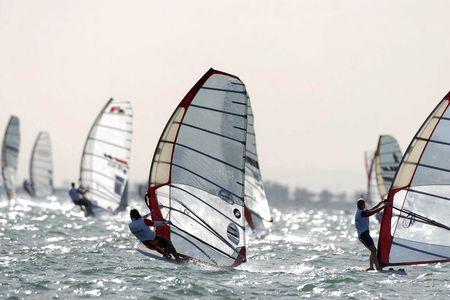 windsurfers: Several windsurfers sail across the bay.