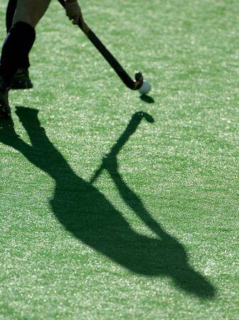 hockey cesped: La sombra de un jugador de hockey sobre hierba, ya que correr por el campo.  Foto de archivo
