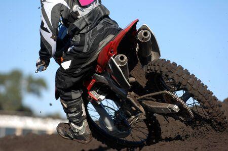 motorcross: Una vista trasera de un corredor MOTOCROSS las razas a trav�s de la suciedad y el barro durante una carrera.