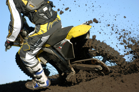 motocross: A rear view of a motocross rider races through the dirt and mud during a race.  Stock Photo