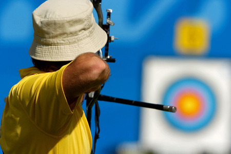 An archer takes aim at a target during competiton. Stok Fotoğraf