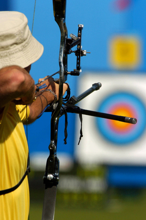 An archer takes aim at a target during competiton. Stock Photo