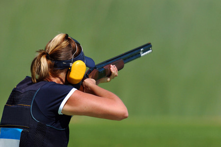A female trap shooter read to shoot a clay pigeon