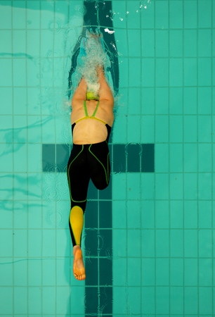 disabled sports: A female multi disability swimmer jumps off the starting blocks