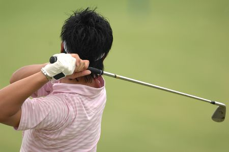 hits: A male golfer hits a ball and is in his back swing. Stock Photo