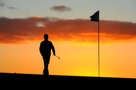 goes: a male golfer goes to remove the flag before he putts at sunrise Stock Photo