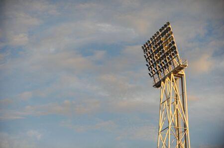Stadium light towers against a setting sky photo