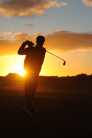 play golf: A male golfer enjoys an early round during sunrise.  Stock Photo