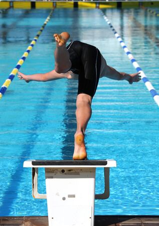 A swimmer dives into the water of a pool. photo