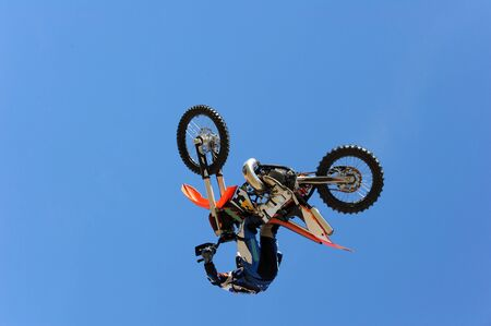A dirt bike rider gets air during a stunt.  photo