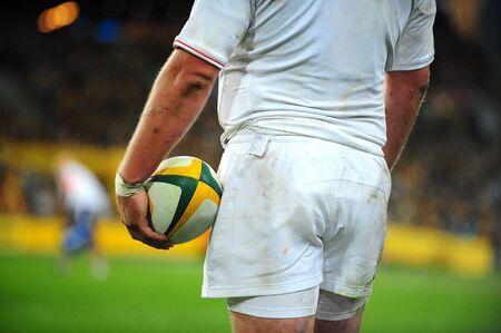 pelota rugby: Un jugador de rugby sostiene el bal�n mientras �l mira fijamente a trav�s del campo. Foto de archivo