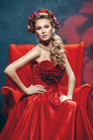 blonde girls: The beautiful girl in a red dress with a graceful wreath on the head Stock Photo