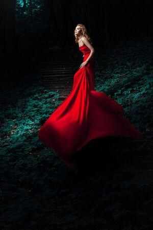 La joven mujer en un vestido rojo en una escalera en la madera Foto de archivo