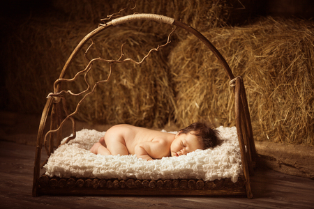 Cute sleeping newborn baby in a wooden lullaby bed on hay background. Studio shot. Stock Photo