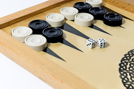 Board game backgammon. Black and white chips on the playing field. Stock Photo