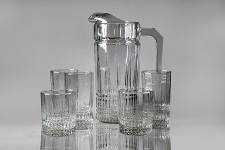 Set of transparent glassware. Pitcher and glasses. Dishes on a beautiful background.