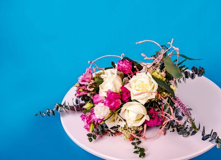 Beautiful bouquet of flowers on white round table on blue background. Zdjęcie Seryjne