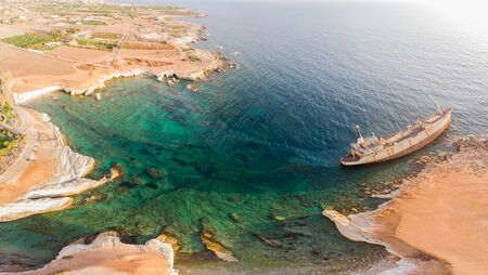 Aerial view of the abandoned ship EDRO III in Pegea, Paphos, Cyprus. Rusty shipwreck stranded on the rocks in intercostal Peyia sea caves, coral Bay, Paphos, standing at an angle to the shore.