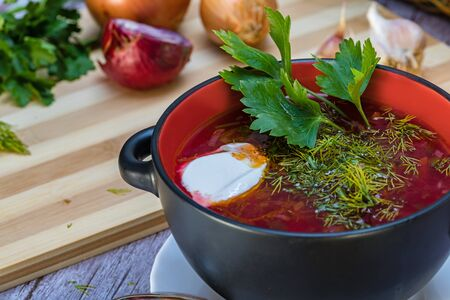 Red borsch, a national dish of Ukrainian cuisine. In the photo, borsch is a black ceramic with sour cream, green onions and garlic on a wooden background.