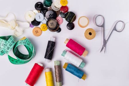 Set of spools of thread, scissors, buttons, fabrics and pins for sewing and needlework on a white background.