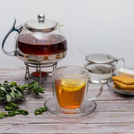 Cup of tea with teapot on a wooden table. Standard-Bild